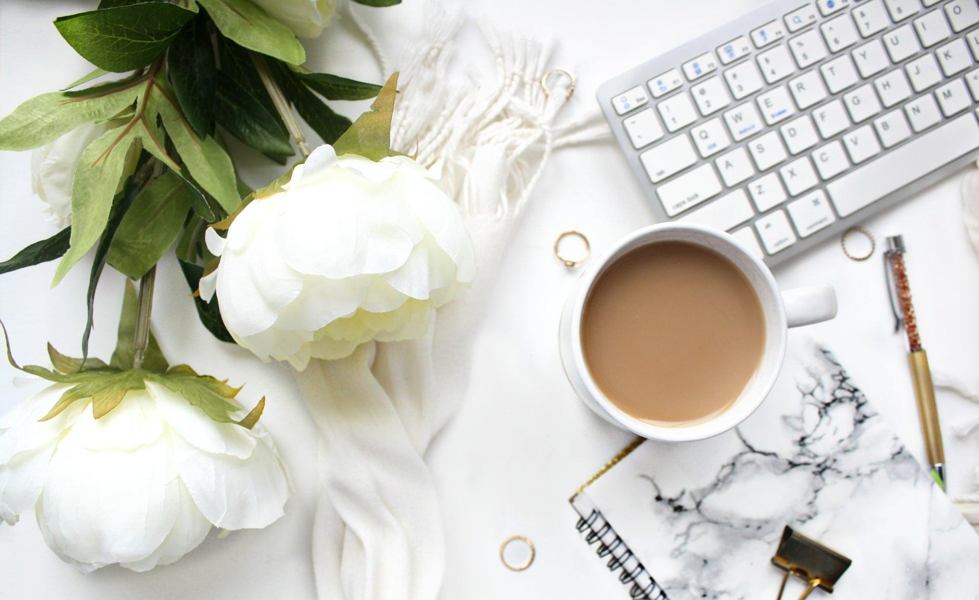 Des pivoines, un clavier, un café d'ordinateur et un stylo posés sur une surface blanche et marbrées