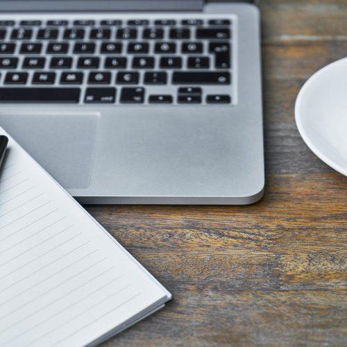 Un ordinateur portable, un café et un carnet sur un bureau en bois brut.